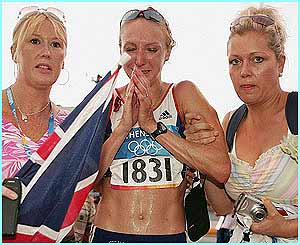 A distraught Paula Radcliffe is lead away by friends after pulling out of the marathon after 23 miles.