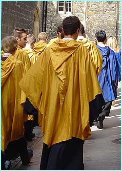 Hogwarts pupils wearing raincoats to cover their robes march out of New College.