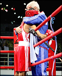 Khan hugs coach Terry Edwards ringside after a rapid victory over his South Korean opponent