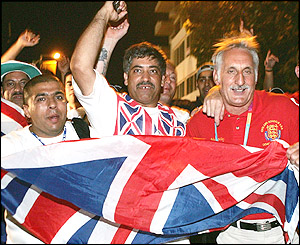 Khan's father Shajaad (centre) leads the celebrations after his son's passage into the lightweight final