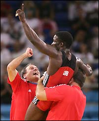 Cuba's Yandro Miguel Quintana celebrates with his coaches after beating Iran's Masuod Jokar of Iran to win gold in the men's 60kg wrestling