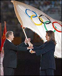 The Mayor of Athens passes on the Olympic flag