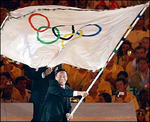 Beijing mayor Wang Qishan takes the Olympic flag