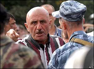 A man speaks to soldiers enforcing an exclusion zone around the school