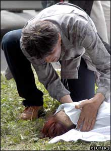 A man grieves over the body of a woman