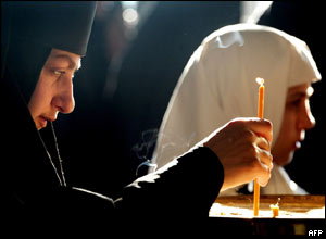A Russian Orthodox nun lights a candle for the victims of the Beslan massacre