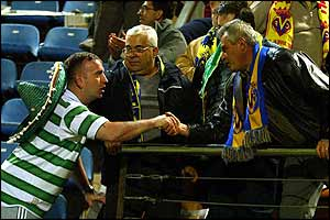 A celtic fan congratulates fans of the other side