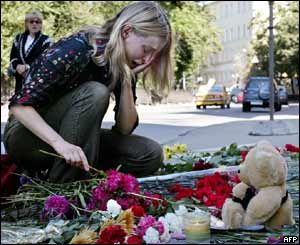 Woman lays flowers in front of the Moscow representative office of North Ossetia region