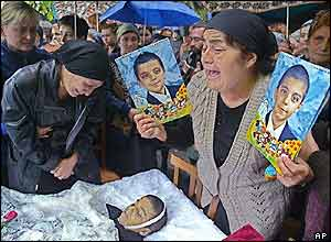 Fedosya Beroyeva, grandmother of 10-year old twins, Soslan (right) and Aslan, cries holding their portraits as their mother Zalina (left)looks at Aslan's body during the twins' funeral