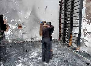 Two girls hug while they stand at the destroyed school gym in Beslan