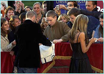 They sign autographs for fans outside the Royal Albert Hall in London where the swanky bash was held