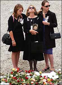 Three women stand at a memorial at Ground Zero