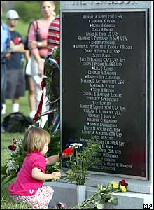 Girl lays a flower at a memorial for the victims of the 9/11 attack in Washington