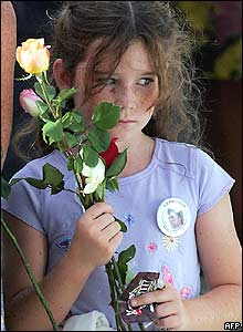 Girl holds a flower during ceremonies at Ground Zero