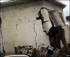 Jamaican man examines his damaged house in Kingston, Jamaica