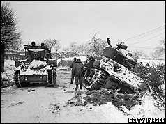 US tanks, one in a ditch, other passing on road