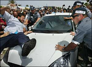 Protesters leap on the car of Mordechai Vanunu