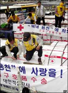 South Korean workers from Korean Red Cross load aid supply kits for North Korea