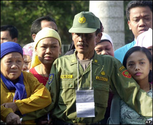 A security officer stands guard as voters wait for their turn in presidential elections at a polling station in Cibubur, south of Jakarta, Sept 20, 2004.
