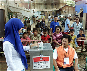Woman votes at a polling station in Jakarta, Indonesia, Monday 20 September