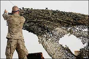 A US marine from the First Battalion, 5th Marines, Bravo Company, takes down netting as his battalion prepares to leave their temporary marine base in the city of Falluja on Friday