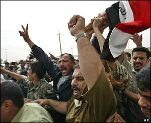 Residents of Falluja celebrate with the Iraqi national flag at a dismantled checkpoint
