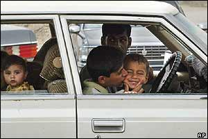 An Iraqi boy kisses a young passenger as they cross into Falluja on Friday
