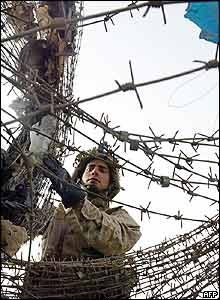 A US marine from the First Battalion, 5th Marines, Bravo Company, cuts down barbed wire
