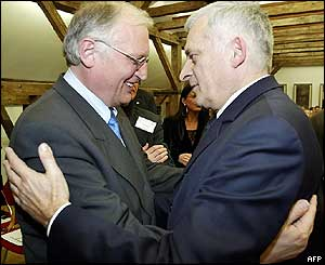 Guenter Verheugen (L), EU Commissioner for Enlargement and former Polish Prime Minister Jerzy Buzek hug during a conference in Warsaw in March