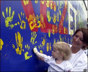 A Hungarian woman holds her daughter as she puts her hand print onto a side of a truck
