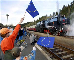 Two Bavarian boys wave EU flags as a special train steams into the railway station across the Czech-German border