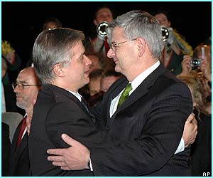 The German and Polich Foreign Ministers Joschka Fischer and Wlodzimierz Cimoszewicz embrace at the bridge between the two countries to to mark Poland's entry.