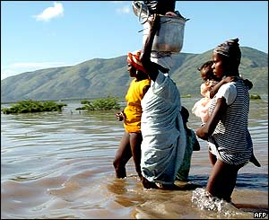 Haitian women wade through water in Gonaives.