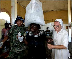 An Argentine UN soldier and a nun help a woman as she is carrying food during a distribution in Gonaives.