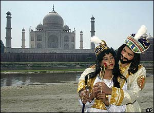 Actors dressed as the Mughal Emperor Shah Jahan and his wife Mumtaz Mahal stand in front of the Taj Mahal