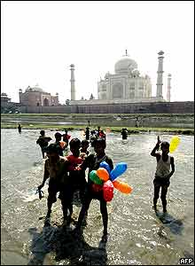Indian children carry the balloons released during the inauguration ceremony to mark the 350th Anniversary of the Taj Mahal on the banks of Yamuna river in Agra.