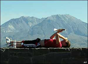 Kim Latschaw, of Gig Harbor, Washington, reads a newspapers as she awaits an eruption from Mount St Helens, 3 October 2004