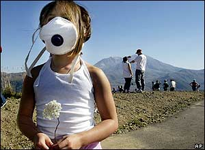 Kiki Kreofski, of Boring, Oregon., holds a flower and wears a dust mask as she stands at the Castle Lake Viewpoint, 2 October 2004