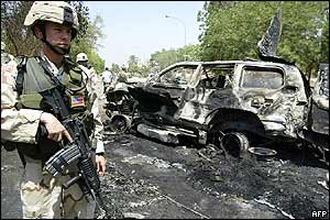 A US soldier in front of burned vehicles