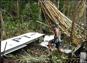 A Brazilian searches amid the wreckage of a plane which crashed in the Amazon jungle near the Colombian border.