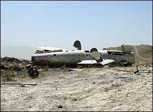 The carcass of an airplane lies in a field near Kabul
