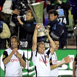 Valencia captain Curro Torres lifts the Uefa cup as his jubilant team-mates start the celebrations
