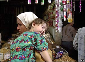 An Iraqi mother and child tour a Baghdad market for provisions