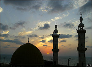 The sun sets behind a mosque in Gaza City.