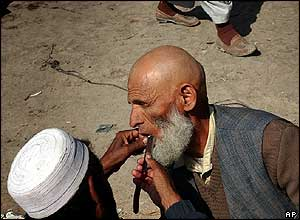 Elderly Afghan gets beard trim