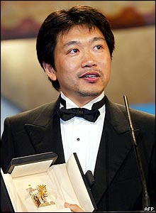 Japanese film director Hirokazu Koreeda accepts the best actor award on behalf of Yagira Yuya for their film Nobody Knows