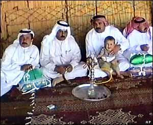 Scene from Iraq wedding video - men in Bedouin robes relax and smoke