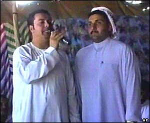 Scene from Iraq wedding video - singer and wedding participant (thought to Hussein al-Ali and bridegroom Azhar Rikad Nayef)