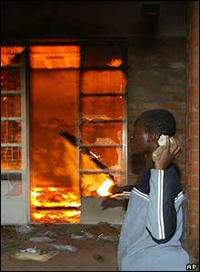 Opposition supporter throws a brick through the burning windows of the UDF office in Ndirande, near Blantyre