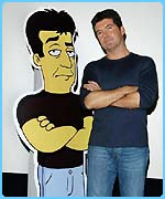 Simon Cowell with a life-size model of himself as a Simpsons character
